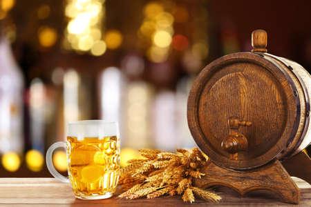 unbottled: Mug and barrel of cold fresh beer on table, on dark pub background