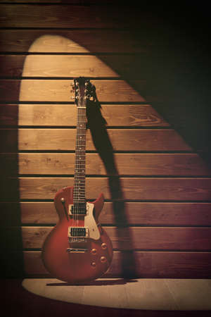 lighted: Electric guitar on dark lighted wooden background