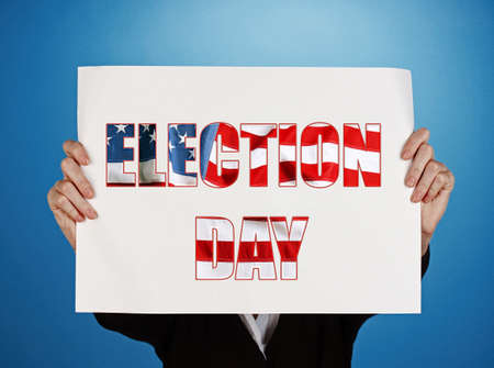 electioneering: Woman holding paper with Election Day text on blue background Stock Photo