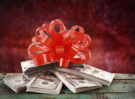 christmas savings: Pile of dollars with bow as gift on red background