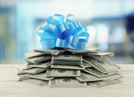 christmas savings: Pile of dollars with bow as gift on bright background