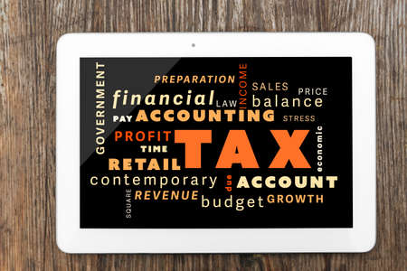 screen savers: Tax concept. Tablet on wooden table Stock Photo