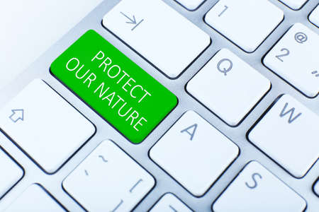 protect: Close-up of laptop keyboard with color button and text Protect Our Nature Stock Photo