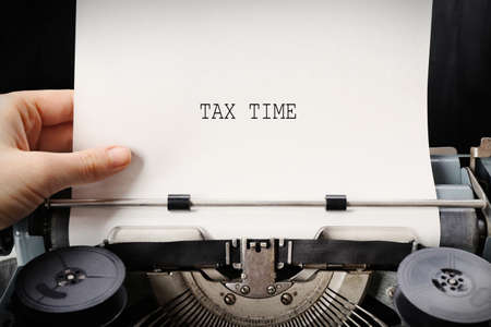 needless: Tax Concept. Hand working on an old typewriter with paper, close up