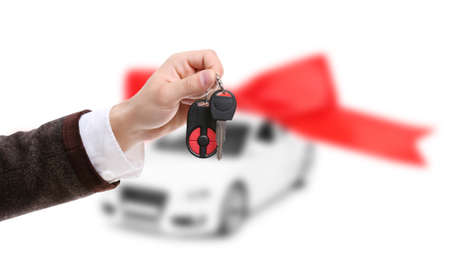 Male hand holding car keys against car background Reklamní fotografie