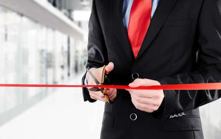 unveiling: Businessman cutting red ribbon with pair of scissors close up