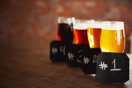 numbering: Glasses with different sorts of craft beer and numbering on wooden table. Retro stylization Stock Photo