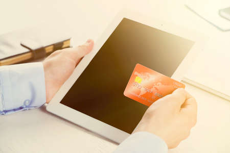 business game: Man holding credit card and tablet on workplace background