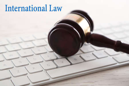 international law: Gavel with computer keyboard on wooden table closeup. International law concept