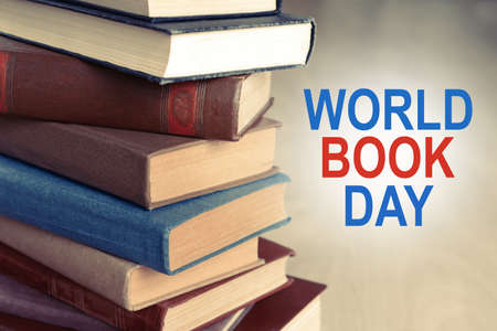 Heap of old books on wooden background. World Book Day poster