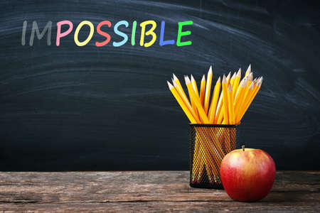 feasible: Word impossible transformed into possible on blackboard and school supplies