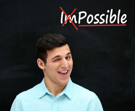 Young man near blackboard with word impossible transformed into possible