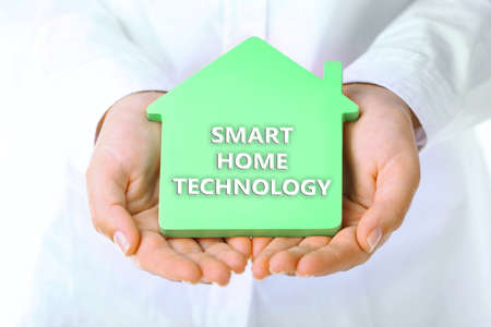 temperature controller: Smart home technology concept. Female hands holding house, closeup