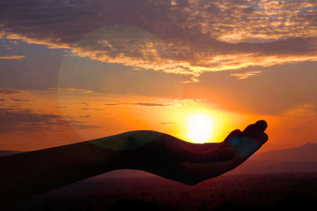 ministration: Silhouette of hand with evening sun