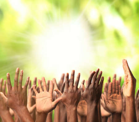 Crowd raising hands on green blurred nature background Stock Photo