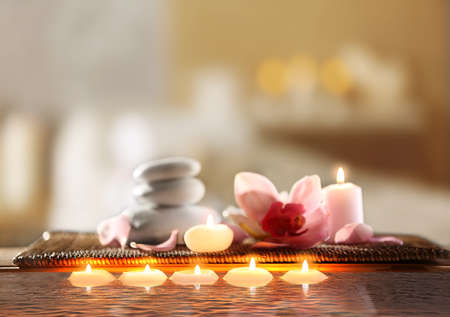 Composition with spa stones, flower and candles in water on blurred background