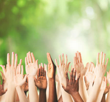 raising hands: Crowd raising hands on green blurred nature background Stock Photo