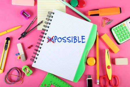 feasible: Word impossible transformed into possible on notebook page with school supplies