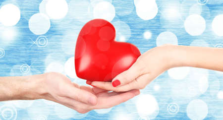 goodness: Female and male hands holding red heart on blurred background. Stock Photo