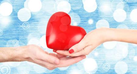 bondad: Manos femeninas y masculinas que sostienen el corazón rojo en fondo borroso.