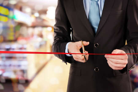 establish: Businessman cutting red ribbon with pair of scissors close up