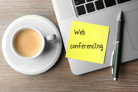 conferencing: Web conferencing written on sticky note, laptop and cup of coffee on table, top view