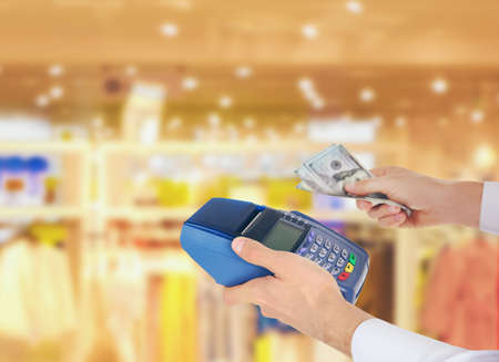 cardreader: Businessman with payment terminal and cash