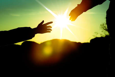 Helping hands with sunlight between two climbers Stock Photo