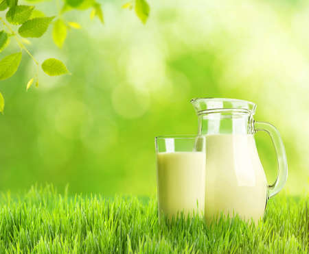 material de vidrio: La leche en recipientes de vidrio en el fondo verde de la naturaleza