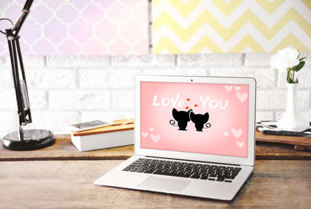 cat s: Modern lamp and laptop with screensaver on table on brick wall background