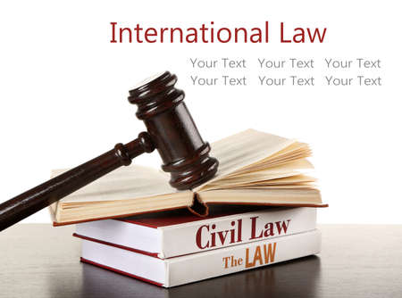 international law: Gavel and books on wooden table on white background. International law concept Stock Photo
