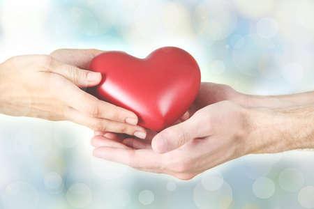 Mujeres y hombres manos sosteniendo el corazón rojo sobre fondo borroso. La familia, el amor y el concepto del cuidado de la salud