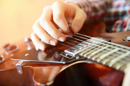 hand jamming: Young man playing electric guitar, close up