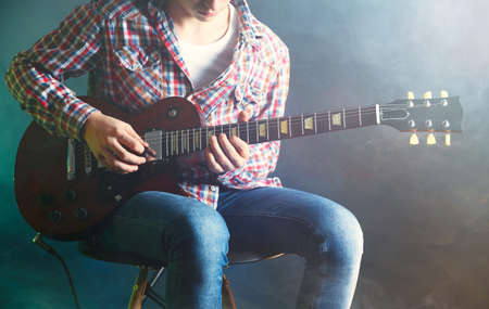 hand jamming: Young man playing electric guitar on lighted foggy background