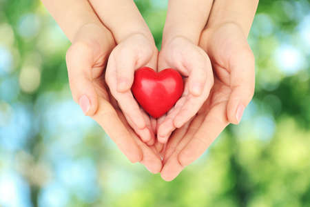 Heart in child and mother hands on green nature background. Concept of taking care, protection, helping and assistance