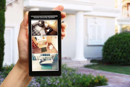 スマート フォンを持っている女性の手には、家の背景がぼやけています。ホーム セキュリティ システムのコンセプト