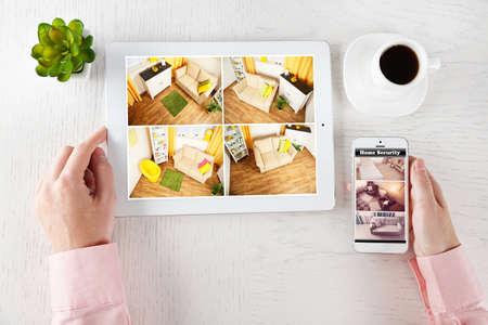 남성 손을 태블릿 및 흰색 테이블에 전화. 가정 보안 시스템 개념