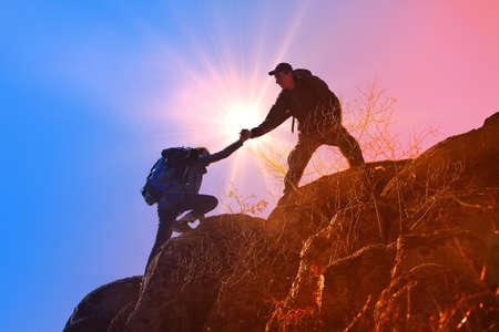 Helpende handen met zonlicht tussen twee klimmers