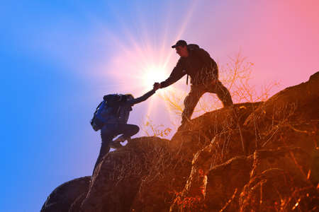 Helping hands with sunlight between two climbers Imagens