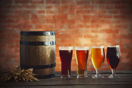 sorts: Glasses with different sorts of craft beer, wooden barrel and barley. Retro stylization