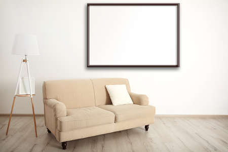 clean home: Beige couch with lamp and empty picture frame on wall background