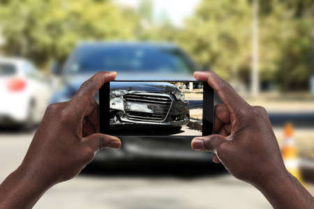 Man photographing his car with damages Stock Photo