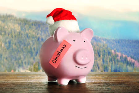 christmas budget: Piggy bank with Santa hat on blurred natural background