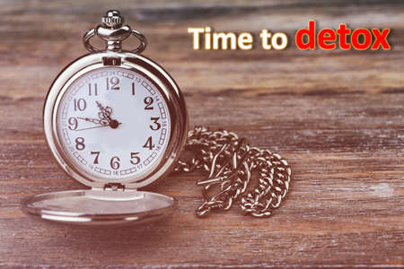 Silver pocket clock on wooden background