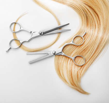 Hairdressers scissors with strand of blonde hair, isolated on white