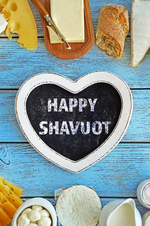Text happy Shavuot in frame of fresh dairy products on blue wooden table Stock Photo