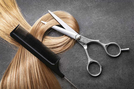 Hairdressers scissors with comb and strand of blonde hair on grey background Imagens