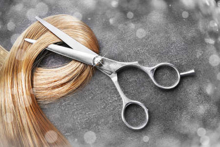 peruke: Hairdressers scissors with strand of blonde hair on grey background