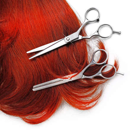 peruke: Hairdressers scissors with strand of red hair, isolated on white Stock Photo