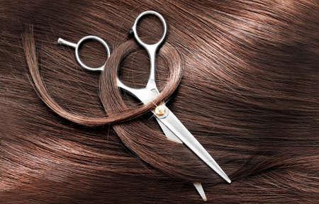 dark brown hair: Hairdressers scissors with dark brown hair, close up
